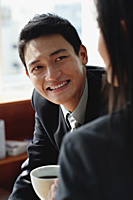 A man smiles as he has coffee with a woman - Asia Images Group