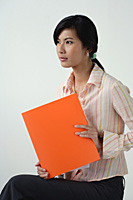 A woman with an orange folder - Asia Images Group