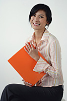 A woman smiles at the camera as she holds an orange folder - Asia Images Group