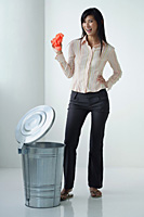 A woman smiles at the camera as she throws something in the rubbish bin - Asia Images Group