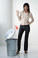 A woman throws something in the rubbish bin - Asia Images Group