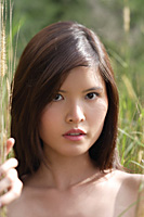 Woman in long grass looking at camera - Asia Images Group