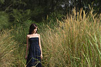 Woman walking in long grass - Asia Images Group