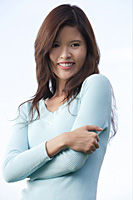 Woman with arms crossed, smiling at camera - Asia Images Group