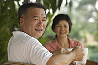 Couple drinking tea in the garden - Asia Images Group