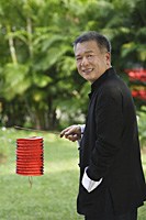 Man in traditional clothing, standing in park holding Chinese lantern - Asia Images Group