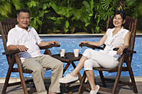 Couple relaxing in deck chairs by the pool - Asia Images Group