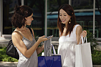 Women with shopping bags having a conversation - Asia Images Group