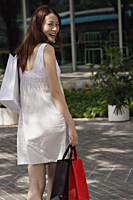 Woman with shopping bags, smiling over shoulder at camera - Asia Images Group