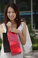 Woman with shopping bags, smiling at camera - Asia Images Group