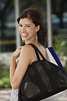 Woman with shoulder bag, smiling at camera - Asia Images Group