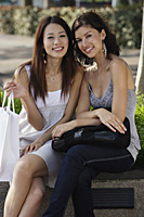 Women sitting on bench, smiling at camera - Asia Images Group