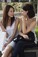 Women sitting on bench, looking at each other - Asia Images Group
