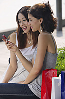 Women sitting on bench, looking at mobile phone - Asia Images Group