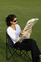 Women on chair, reading newspaper - Asia Images Group
