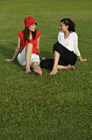 Young women in park, looking at each other - Asia Images Group
