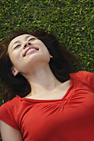 Woman smiling, lying on grass - Asia Images Group