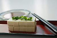 Still life of stacks of sliced beancurd with spring onion - Asia Images Group