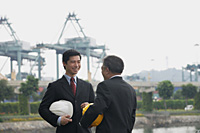 Businessmen with helmets having a conversation - Asia Images Group