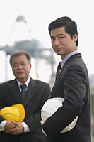 Businessmen with helmets looking at camera - Asia Images Group