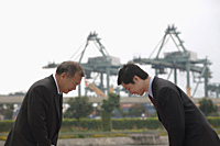 Businessmen standing face to face, bowing - Asia Images Group