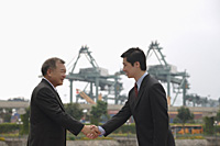 Businessmen standing face to face, shaking hands - Asia Images Group