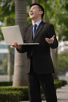 Businessman holding laptop and laughing - Asia Images Group