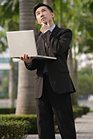 Businessman with quizzical expression, holding laptop and looking up - Asia Images Group