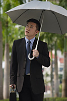 Businessman holding umbrella - Asia Images Group