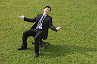 Businessman sitting on an office chair, smiling at camera - Asia Images Group