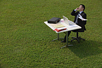 Businessman on the phone while sitting at desk - Asia Images Group