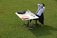 Businessman taking a break at desk - Asia Images Group