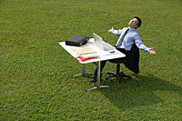 Businessman relaxing at office desk - Asia Images Group