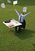 Businessman sitting at desk and throwing paper in the air - Asia Images Group