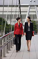 Businesswomen walking together while talking - Asia Images Group