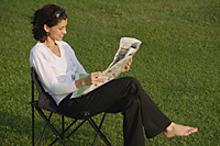 Woman reading newspaper in the park - Asia Images Group