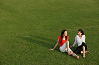 Two women relaxing in the park - Asia Images Group