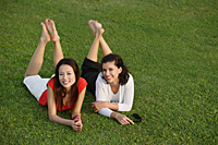 Two women relaxing in the park, looking at camera - Asia Images Group