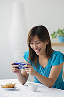 Young woman playing on handheld game console - Asia Images Group