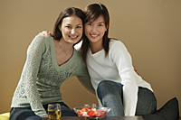 Friends with arms around each other smiling at camera - Asia Images Group