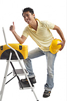 Builder standing on ladder and giving thumbs up - Asia Images Group