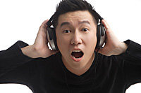 Man with headphones looking surprised at camera - Asia Images Group