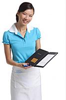 Waitress presents bill, smiling at camera - Asia Images Group