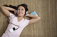 Young woman listening to music while lying down - Asia Images Group