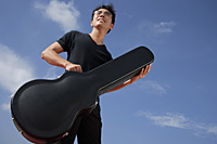 Man holding guitar case - Asia Images Group