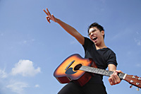 Man playing guitar outdoors - Asia Images Group