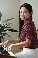 Young woman playing keyboard - Asia Images Group