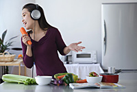 Young woman singing into carrot - Asia Images Group