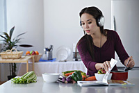 Young woman cooking while listening to music - Asia Images Group