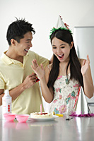 Young woman being surprised with birthday cake - Asia Images Group